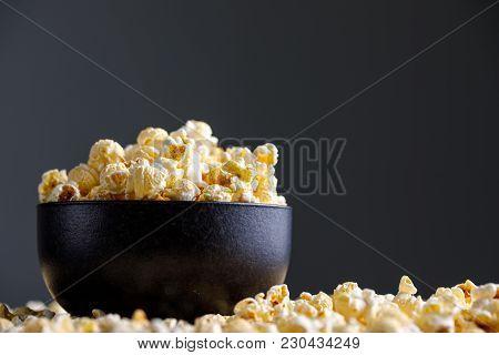 Popcorn In A Black Ceramic Bowl And Around It.