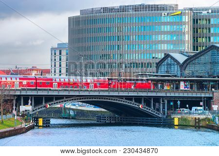 Berlin, Germany - December 8, 2017: Business Downtown, Red Train And Bridge Over Spree River, Berlin