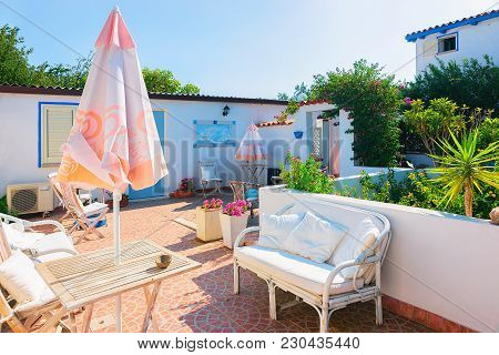 Cugnana, Italy - September 8, 2017: Courtyard Garden With Table And Chairs In The House At Costa Sme