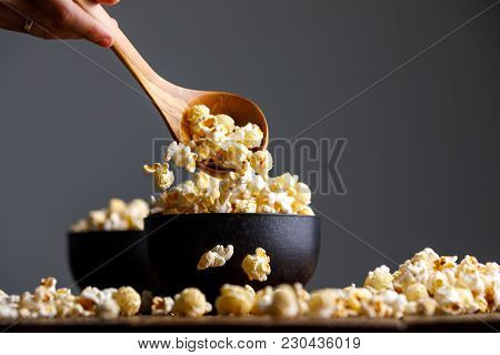 Popcorn Falls From A Wooden Spoon Into The Cups And Around Them.