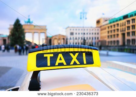 Taxi Sign Board In The Street Of Berlin, Germany. Brandenburg Gate On The Background