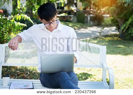 Young Business Man Sitting On The Park Bench With Laptop On His Laptop In The Middle Of A Green Mead