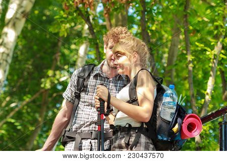 Two Young People Tourists Hiking Walking Outdoor. Man And Woman With Trekking Poles Sticks.