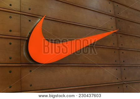 Brasov, Romania-10 March 2018: Orange Nike Logo On Wooden Background Close Up Shot  On The City Mall