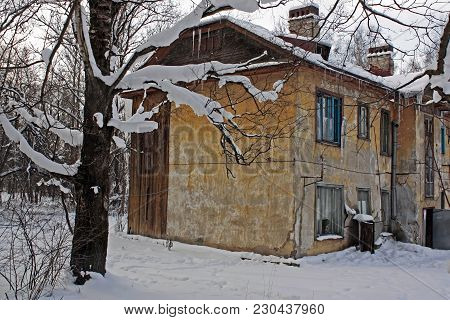 Old Two-storey House With Yellow Walls And Repulsed Plaster, Broken Windows And Chimney On The Roof