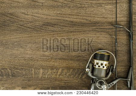 Fishing Tackle On Wooden Background. The Spool And Rod Located On The Right. Top View.