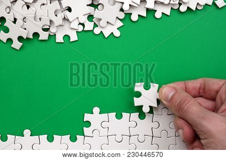 The Hand Folds A White Jigsaw Puzzle And A Pile Of Uncombed Puzzle Pieces Lies Against The Backgroun
