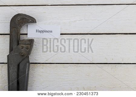 Pipe Wrench Compresses A Piece Of Paper With An Inscription Happiness. Toned Image