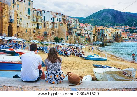 Cefalu, Italy - September 26, 2017: Young Couple Sitting At The Beach In Cefalu Old Town, Palermo Re
