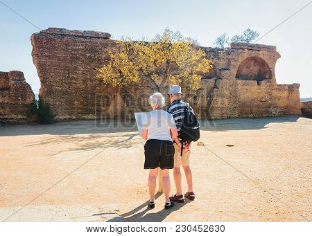 Senior Couple Reading Map At Stone Necropolis In The Valley Of Temples In Agrigento, Sicily, Italy