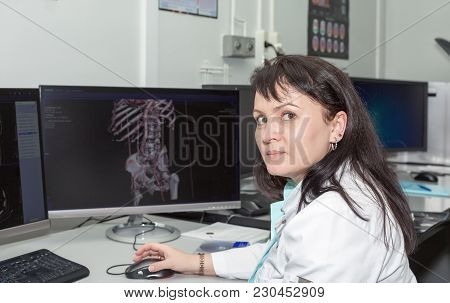 A Brunette Female Doctor Examining Ct Scanner Results