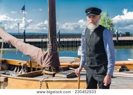 Urk, The Netherlands - September 02, 2017: Old Sailor With Stick, Cap And Beard Standing For Traditi