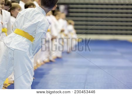 Children In Kimono Standing In A Long Line On Tatami On Martial Arts Seminar. Selective Focus