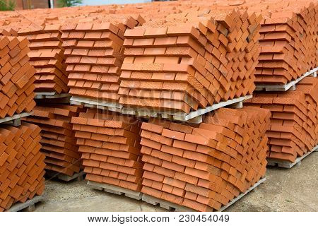 Red Bricks Stacked Into Cubes. Red Blocks Of Bricks In Stock. Warehouse Bricks. Bricks Lie At An Ang