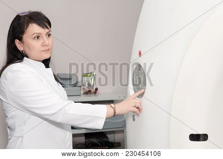 A Female Doctor Pushing Control Button On Ct Scanner. Computerised Tomography