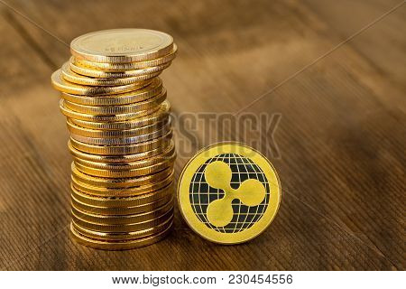 A Single Gold Ripplecoin Digital Coin Standing On Edge Alongside A Stacked Pile Of Coins In A Concep
