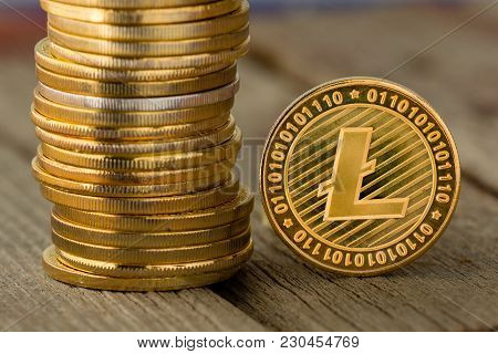 Detail Of A Litecoin Gold Cryptocurrency Coin Standing On Edge Alongside A Tall Stack Of Coins In A