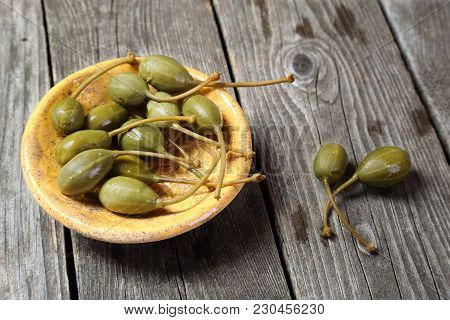 Capers In A Yellow Ceramic Plate On A Gray Wooden Table