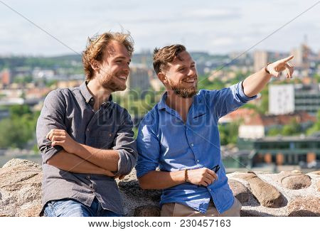 Young Man Showing Something Interesting To His Friend As Travel And Friendship Concept, Vilnius, Lit