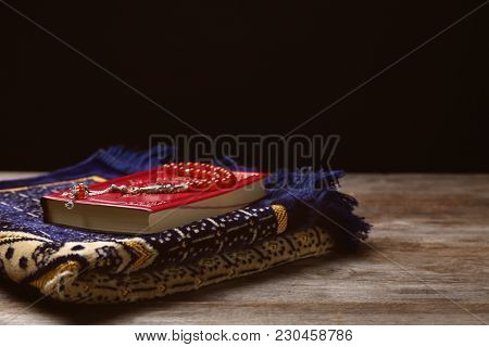 Holy book of Muslims, prayer beads and rug on wooden table