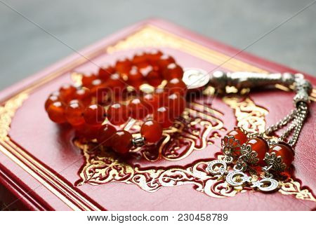 Holy book of Muslims and prayer beads, closeup