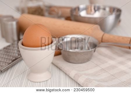 Chicken egg and cooking utensils on table