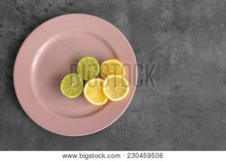 Plate with cut lemon and lime on grey background