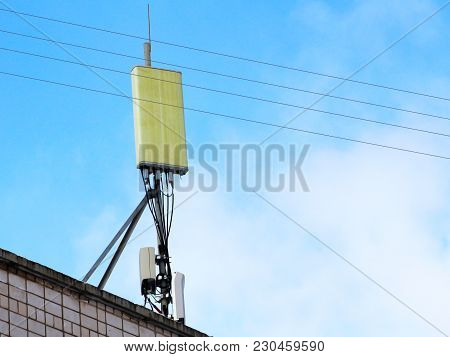 Mobile Antenna In The Roof Of A Building, Against Blue Sky, Tehnology