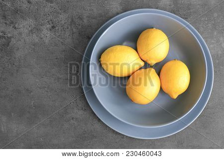 Plates with lemons on grey background