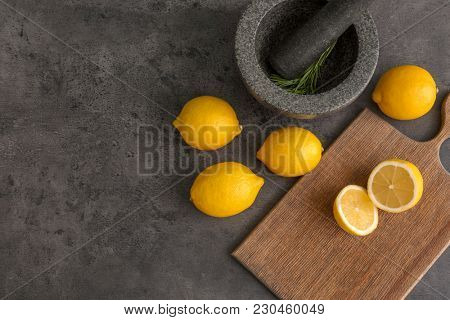Stone mortar, cutting board and lemons on grey background. Cooking utensils