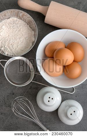 Cooking utensils and products on grey background