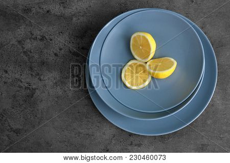 Plates with cut lemon on grey background
