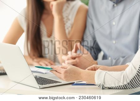 Young couple discussing pension plan with consultant, closeup