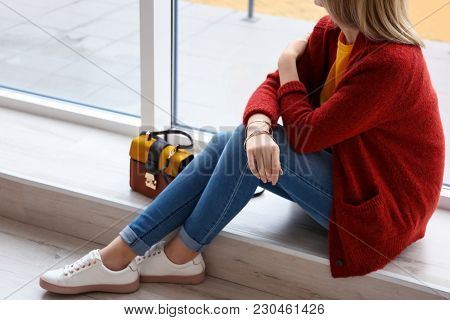 Young woman in red cardigan near window indoors