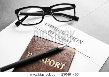 Passport, glasses and sheet of paper with words IMMIGRATION REFORM on table