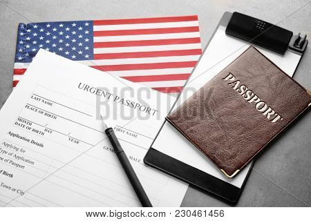 Passport, American flag and application form on table. Immigration to USA