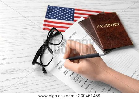 Woman filling urgent passport application form near American flag at table. Immigration to USA