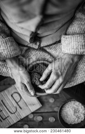 Poor woman holding bowl with some bread, focus on hands. Black and white effect
