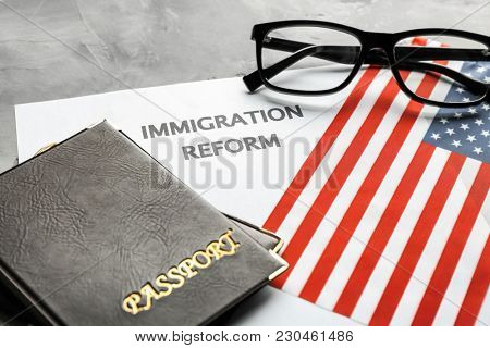 Passports, American flag and sheet of paper with words IMMIGRATION REFORM on table