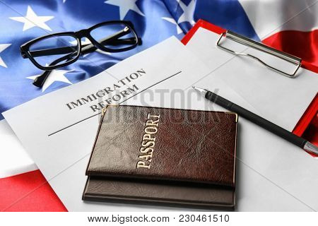 Passports and sheet of paper with words IMMIGRATION REFORM on American flag