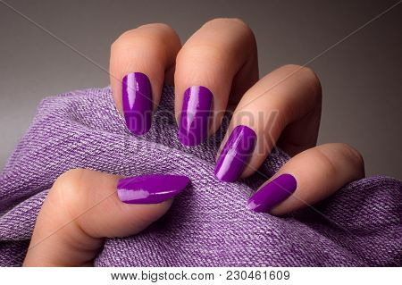The Female Hand With Purple Nails Is Holding Purple Denim Textile On Gray Background. Manicure Conce