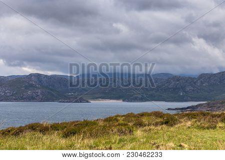 Laide, Scotland - June 8, 2012: Blue Atlantic Ocean Cuts Deep Into Rough Dark Mountain Shorelines Un