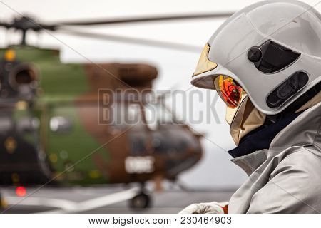 Flight Crew Fireman With Helmet And Reflecting Visor And Fire Fighting Gear Wait To Conduct Flight O