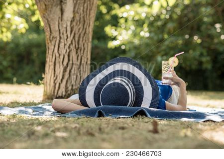 Woman Spending A Relaxing Day In The Garden Lying In The Shade Of A Tree In Her Large Brimmed Sunhat