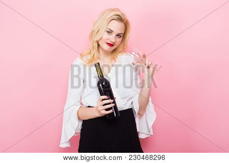 Portrait Of Attractive Skinny Blonde Woman With Red Lips In White Blouse And Black Trousers On Pink