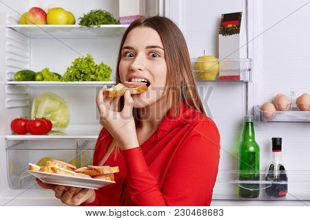 Hungry Adorable Woman Eats Delicious Sandwhiches With Cheese And Sausage, Stands Near Opened Refrige