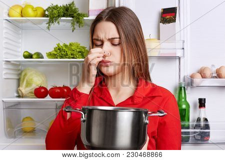 Young Brunette Woman With Displeased Expression Smells Spoiled Soup In Stew Pan, Feels Musty Smell A