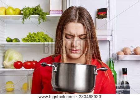 Angy Displeased Female Housewife Looks In Pot With Foul Meal, Smells Unpleasant Stink, Stands Near F