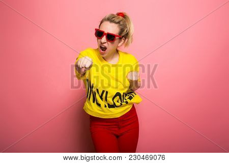 Attractive Woman In Yellow T-shirt, Red Jeans And Sunglasses Showing Her Fists Ready To Fight Isolat