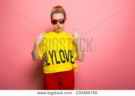 Woman In Yellow T-shirt, Red Jeans And Sunglasses Pointing With Fingers At Herself Isolated On Pink
